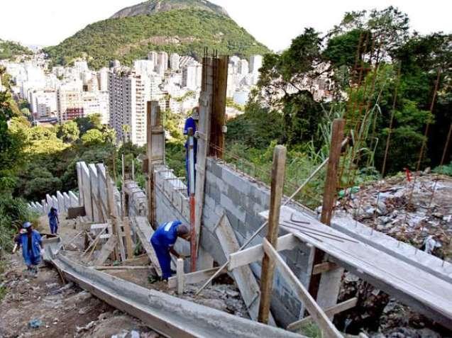 Grupo de homens trabalha em construção de muro na favela Santa Marta, no Rio de Janeiro © AFP