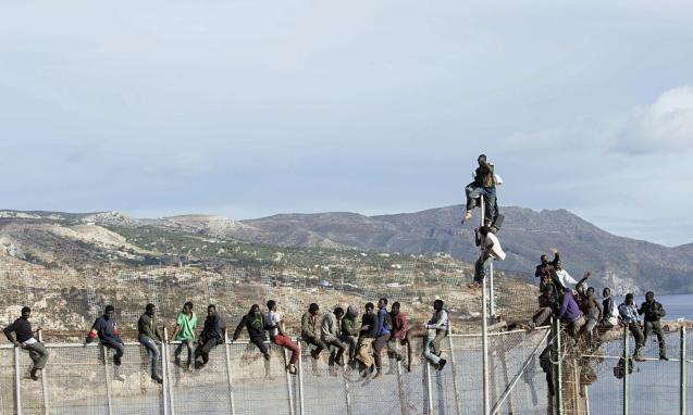 Would-be immigrants sit on a fence at the Spanish-Moroccan border as they try to enter Melilla. © Juan Rios/Neupic/EPA