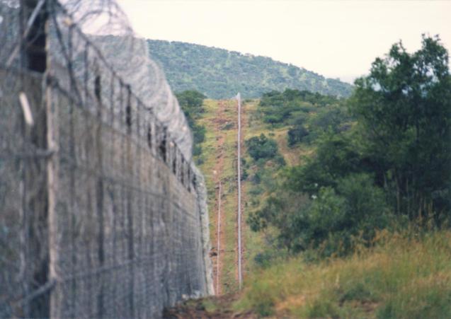 """A""""Cobra de Fogo"""" ou""""Khaftan"""" (Morte), na fronteira entre Moçambique a África do Sul . Este muro ou barreira de separação estende-se desde o rioSatara River até à Suazilândia. Aqui estava ainda em fase de construção. © withmaliceandforethought.com/html/"""