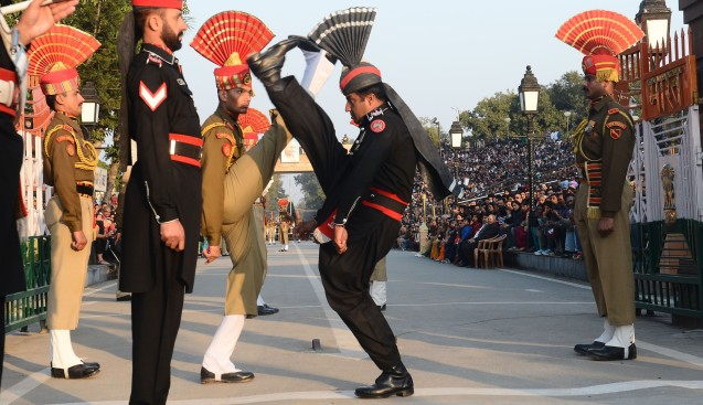 "Pakistani Rangers (in Black) and Indian Border Security Force personnel (in Brown) perform the 'flag off' ceremony at the Pakistan-India Wagah Border Post on January 15, 2013. Indian Prime Minister Manmohan Singh warned Tuesday that there ""cannot be business as usual"" with neighbouring Pakistan after last week's deadly flare-up along the border in disputed Kashmir. © AFP PHOTO/Arif ALI"