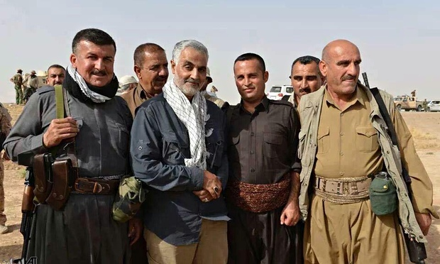 Qassem Suleimani (centre, with revolutionary scarf), the commander of the elite Revolutionary Guards Quds force, poses with a group of peshmerga fighters in Kurdistan. © IRNA | The Guardian