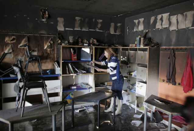 A woman inspects the damage on the aftermath of an arson attack that targeted first-grade classrooms at a Jewish-Arab school in southern Jerusalem. Scrawled on the walls were offensive slogans in Hebrew reading 'Death to Arabs' and 'There's no coexistence with cancer'. © AFP