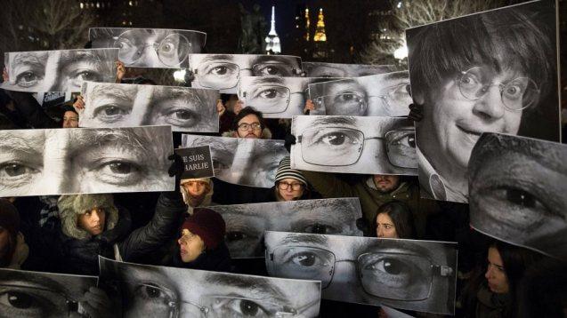 Fotos dos cartoonistas mortos pelos terroristas em Paris erguidas por manifestantes, que seguram também um cartaz com a palavra de ordem Je suis Charlie. © John Michillo | AP terroristas em Paris