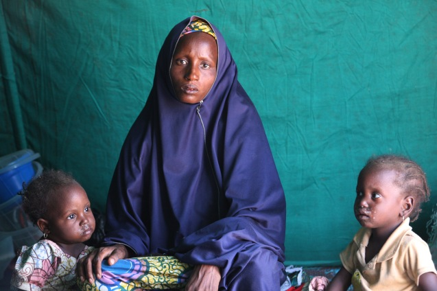 In this photo taken Monday, Dec. 8, 2014, a Nigerian woman, Halima Ibrahim and her children sit at a camp for displaced people in Gagamiri, Niger, after her husband was killed by an Islamic extremist in Damassak. With a military escort instead of the usual pomp, the Emir of Mubi was reinstalled Friday in his palace, where until recently the black-and-white flag of Nigeria's Islamic extremists, Boko Haram, flew. An army tank now guards Mubi's town gate fortified by sandbags, as residents return from the mountain hideouts where they hid while their city was held for more than a month by the Islamic extremists. ( © Delafortrie Anouk | AP