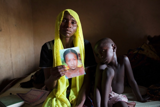 Rachel Daniel, 35, holds up a picture of her abducted daughter Rose Daniel, 17, as her son Bukar, 7, sits beside her at her home in Maiduguri in northeast Nigeria on May 21, 2014. Rose is one of the more than 200 of her classmates on April 14 by Boko Haram militants from a secondary school in Chibok, Borno state. © Joe Penney/Reuters