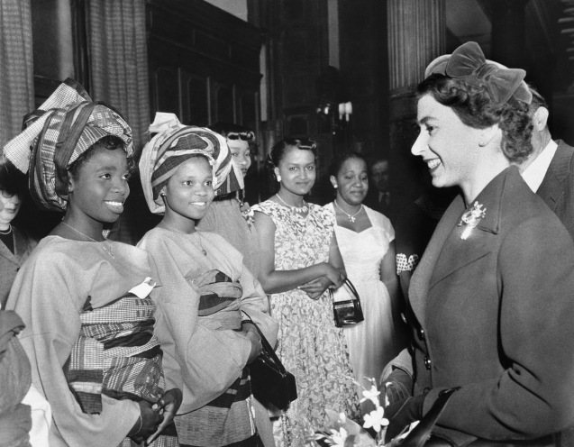 Queen Elizabeth II chats with this pair of colonial students when she visited the British council?s student hostel in London on Dec. 13, 1955, where 350 colonial men and women are students. The occasion of her visit was to help celebrate the 21st anniversary of the council. The two students, dressed in their colorful native garb are, Flanlayo Williams. 22, of Lagos, left, and Miss R. Sekoni Williams, of Ibadan, Nigeria. Others are unidentified. © AP
