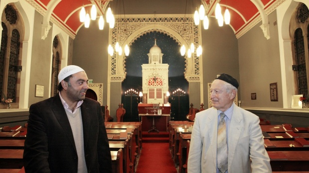 "Zulfi Karim, secretary of Bradford Council of Mosques, and Rabi Rudi Leavor inside Bradford Synagogue, a model of cross-cultural co-operation. According to British daily The Guardian, Rudi Leavor, the synagogue's 87-year-old chairman, reluctantly proposed the nuclear option: to sell the beautiful 132-year-old building, forcing the congregation to go 10 miles to Leeds to worship. It was a terrible proposition, coming just after the city's only Orthodox synagogue had shut its doors in November 2012, unable to regularly gather 10 men for the Minyan, the quorum of 10 Jewish male adults required for certain religious obligations. But rather than close, Bradford Reform Synagogue's future is brighter than ever after the intervention of Bradford's Muslim community, which according to the 2011 census outnumbers the city's Jews by 129,041 to 299. A fundraising effort – led by the secretary of a nearby mosque, together with the owner of a popular curry house and a local textile magnate – has secured the long-term future of the synagogue and forged a friendship between Bradfordian followers of Islam and Judaism."" ©Gary Calton"