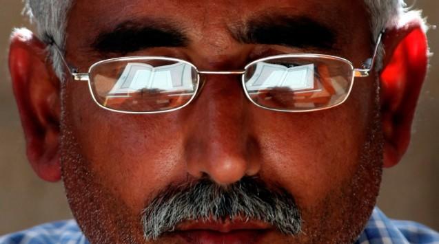 O Corão, livro sagrado dos muçulmanos, está reflectido nos óculos de um crente, em Amã, na Jordânia. Um interesse crescente por obras não religiosas, de autores como Sartre e Camus, têm contribuído para que muitos no Médio Oriente questionem velhas crenças, tornando-se agnósticos ou ateus. E não é um fenómeno exclusivo de países árabes, onde predomina a ortodoxia sunita, mas sobretudo no, maioritariamente persa e xiita, Irão (onde o poeta Hafez é tão venerado como Maomé). © Mohammad Hannon | AP