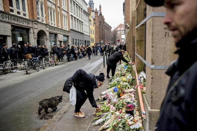 People lay flowers outside a synagogue where an attack took place in Copenhagen, Sunday, Feb. 15, 2015. Danish police shot and killed a man early Sunday suspected of carrying out shooting attacks at a free speech event and then at a Copenhagen synagogue, killing a Danish documentary filmmaker and a member of the Scandinavian country's Jewish community. Five police officers were also wounded in the attacks. © Rumle Skafte | AP|DENMARK OUT