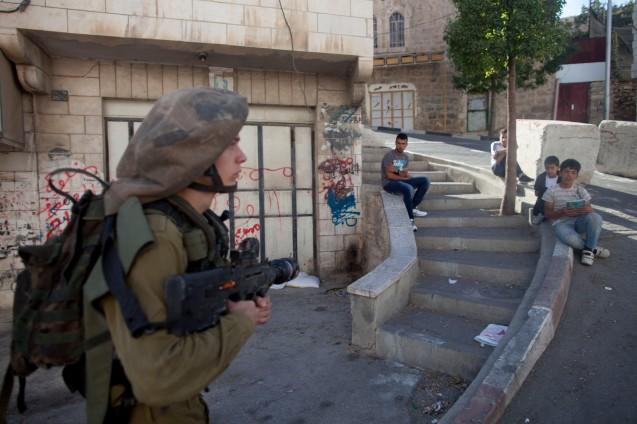 Hebron, na Cisjordânia ocupada por Israel: Crianças observam e são observadas por um soldado na cidade onde só os judeus têm liberdade de movimentos. Durante a campanha eleitoral, Netanyahu prometeu que, so a sua liderança, Israel jamais permitirá a criação de um Estado aos palestiniano. © Lior Mizrahi |Getty Images