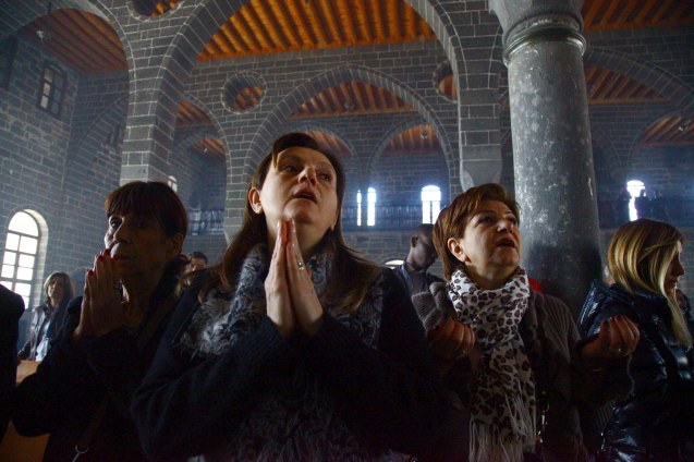 """Armenian Christian women pray during an Easter mass at Surp Giragos church in Diyarbakir, in the Kurdish-dominated southeastern Turkey. Kurds are helping to rebuild churches, putting up Armenian candidates for national elections and apologizing for their forebears – who participated in the massacres of Armenians in southeast Turkey during World War One in return for promises of Armenian property in this world and a place in the next for killing non-believers. Crucially, the Kurds recognize the massacres that began 100 years ago this week as a genocide. This contrasts to the rest of the country, where most Turks reject Armenian assertions that 1.5 million of their people were slaughtered in a genocide. Picture taken on April 5, 2015. © Sertac Kayar 