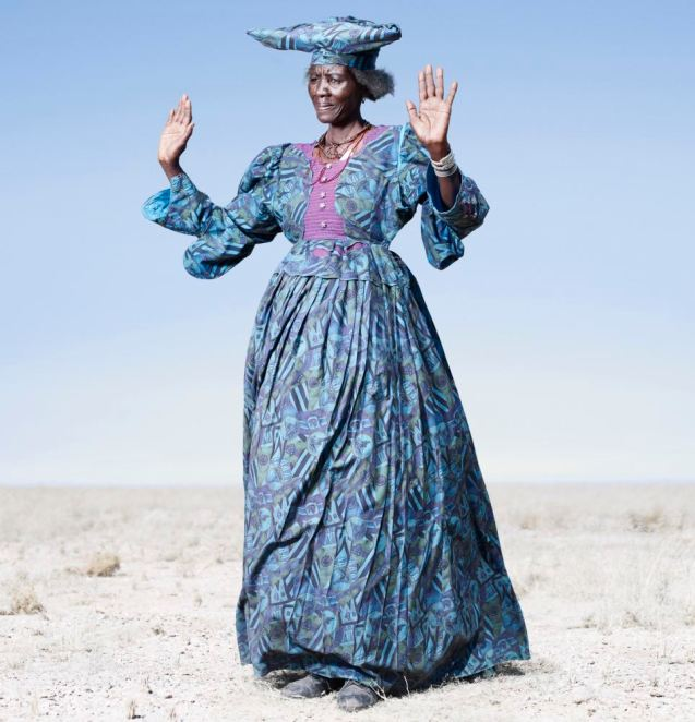 Costume drama: Herero woman in blue dress in cow dance pose © Jim Naughten