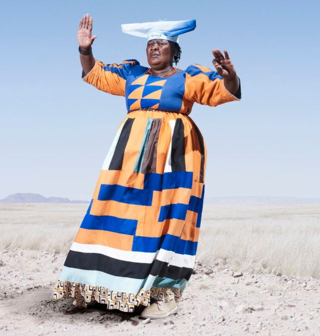 Herero woman in orange dress, adopting the traditional cow pose Read more: http://www.dailymail.co.uk/news/article-2286624/The-Namibian-women-STILL-dress-like-colonists-Tribe-clings-19th-century-dress-protest-Germans-butchered-them.html#ixzz3YHMbyhOO Follow us: @MailOnline on Twitter | DailyMail on Facebook ©