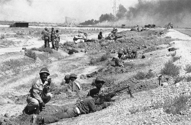 September 22, 1980: Iraq invades Iran, leaving Iran diplomatically isolated from the West, supporting Iraq, for the better part of the decade. A cease-fire wasn't declared until 1988, after an estimated 1 million lives were lost. Above: Iraqi troops entrenched along the highway connecting Abadan with Khorramshahr on Oct. 19, 1980 while smoke drifting in background comes from an oil refinery near Abadan, which was set by Iraqi artillery bombardment. © NBC News