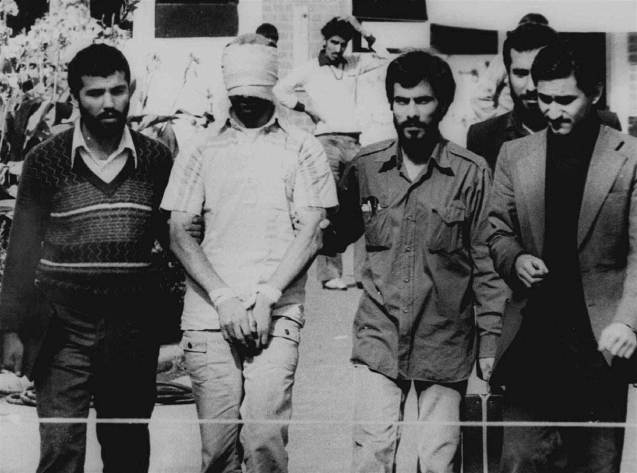 Above: One of the hostages seized when Islamic radicals stormed the U.S. Embassy in Tehran, blindfolded and with his hands bound, is displayed to the crowd outside the U.S. Embassy in Tehran by the Iranian hostage-takers on Nov. 9, 1979. @
