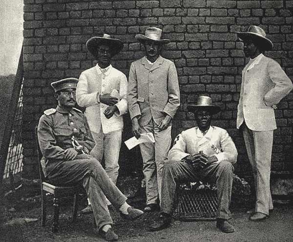 Theodor Leutwein (seated left), Zacharias Zeraua (2nd from left) and Manasseh Tyiseseta (seated, fourth from left), in 1895. ©commonswiki