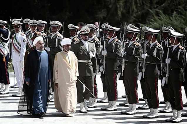 O Presidente iraniano Hassan Rowhani (à esquerda) e o Sultão de Omã passam revista a tropas de honra durante a visita do líder omanita ao Palácio de Saadabad em Teerão, a 25 de Agosto de 2013. © Behrouz Mehri | AFP | Getty Images