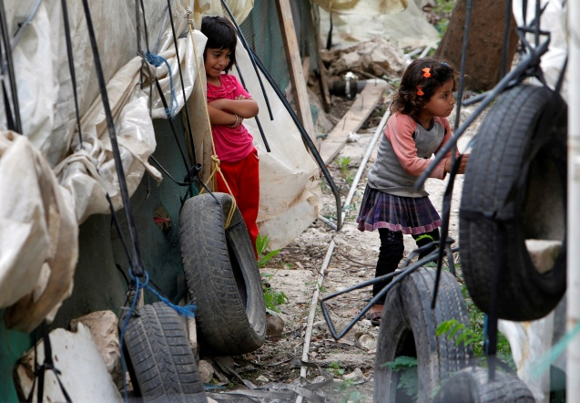 Syrian refugee children stand outside their tents in Zahrani village, southern Lebanon, May 3, 2016 © Ali Hashisho   Reuters RTX2CNIX