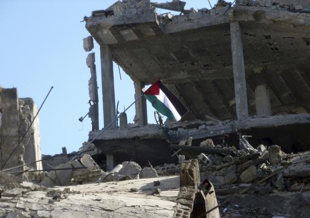 Bandeira palestiniana içada nas ruínas de um edifício no campo de refugiados de Yarmouk, a sul de Damasco, submetido a um cerco do Daesh e das tropas de Assad. © Reuters
