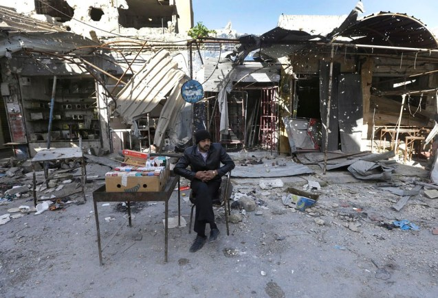 A Syrian street vendor who sells cigarette boxes, sits in front of destroyed shops which were damaged by the shelling of the Syrian forces, at Maarat al-Nuaman town, in Idlib province, on February 26, 2013. Syrian rebels battled government troops near a landmark 12th century mosque in the northern city of Aleppo on Tuesday, while fierce clashes raged around a police academy west of the city, activists said. © Hussein Malla | AP
