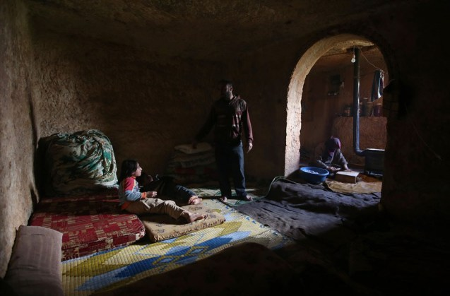A father speaks with his children in an underground Roman tomb which he uses with his family as shelter from Syrian government forces, at Jabal al-Zaweya, in Idlib province, on February 28, 2013. The ancient sites are built of thick stone that has already withstood centuries, and are often located in strategic locations overlooking towns and roads. © Hussein Malla | AP