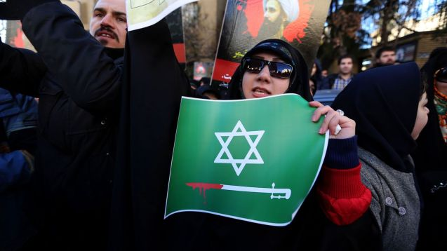 An Iranian woman holds an anti-Saudi placard at a protest outside the Saudi embassy in Tehran. Behind her is a photo of Shia cleric Nimr al-Nimr, whom Saudi Arabia executed ©Atta Kenare | AFP | Getty Images