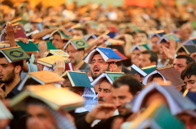 Shi'ite Muslims place copies of the Koran on their heads during a ceremony marking the death anniversary of Imam Ali at his shrine in the holy city of Najaf, about 160 km (100 miles) south of Baghdad © Ahmad Mousa | Reuters