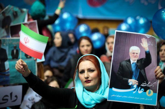 Uma iraniana ergue um cartaz da Coligação Universal dos Reformistas, num comício em Teerão_ o azul turquesa foi uma das cores da campanha © Fatemeh Bahrami Anadolou | Getty