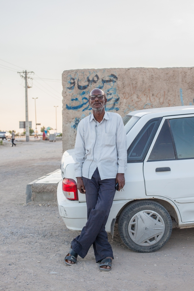 In Bandar Abbas, Eshagh is leaning against one of the most sold cars in Iran, a Kia Pride. The nearly extinct cult car is the Peykan. © Courtesy of Mahdi Ehsaei