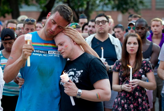 Ryan Gibson, left, embraces Tabor Winstead during a vigil for the victims of the Orlando shooting on Sunday, June 12, 2016 at the Legends Club on Hargett Street in downtown Raleigh, N.C. The event was held by the LGBT community in Raleigh, after 50 people were killed in an Orlando nightclub. ( © Robert Willett |The News & Observer via AP