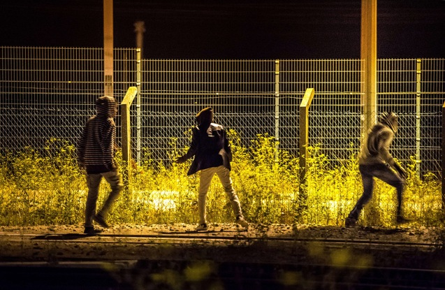 Migrants that have passed a first fence look for another passage to access the Eurotunnel terminal on August 6, 2015 in Frethun near Calais, northern France © Philippe Huguen | AFP | Getty